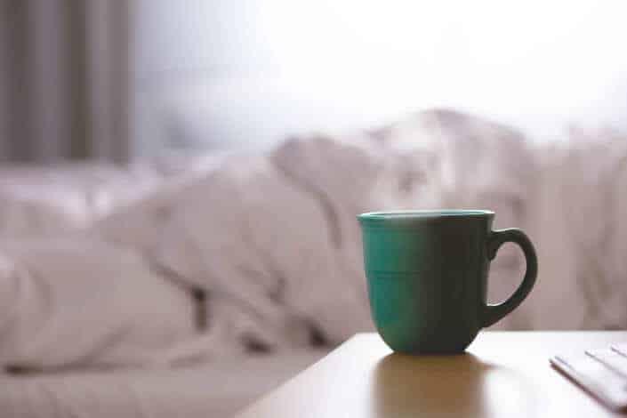 taza verde caliente al lado de la cama