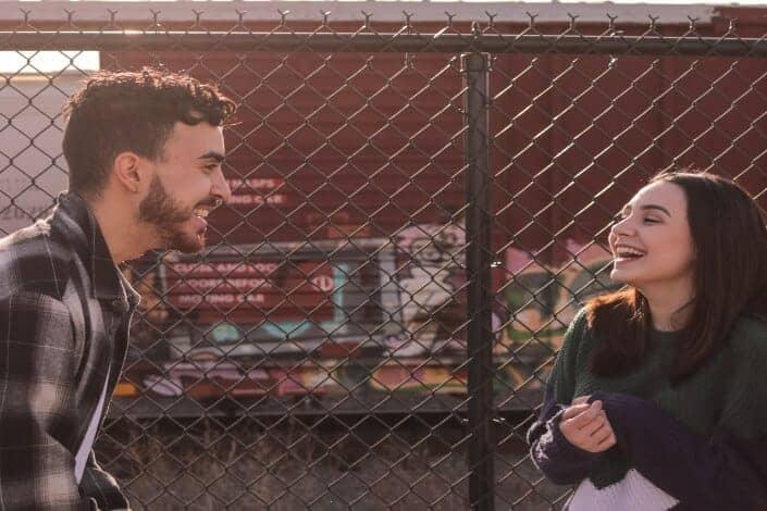 pareja riendo frente a la valla