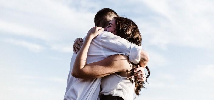 pareja abrazándose con fondo de nubes