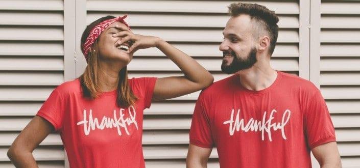 Pareja vistiendo camisetas agradecidas a juego y divirtiéndose