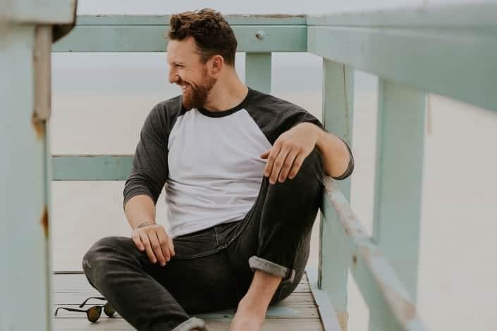 Hombre con ropa casual sentado en una esquina del porche
