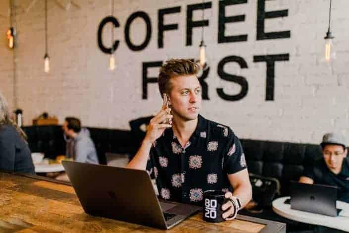 cafetería con hombres ocupados trabajando en su computadora portátil