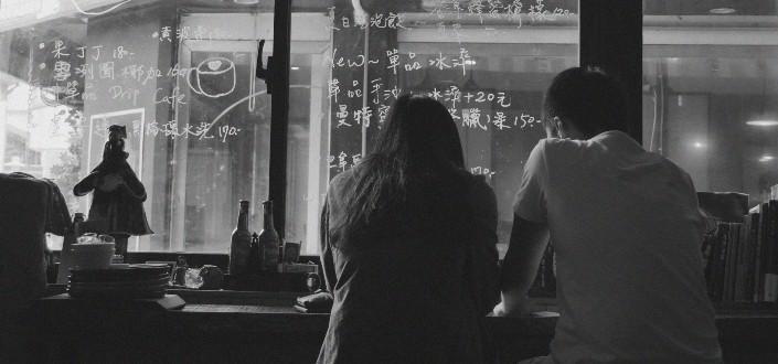 Fotografía en blanco y negro de un hombre y una mujer relajándose en un café chino