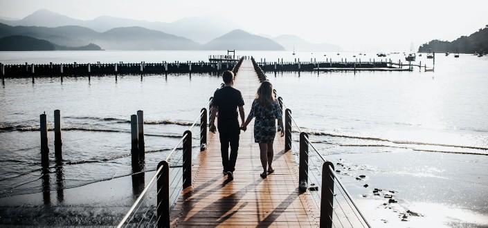 pareja caminando de la mano en un puente del lago