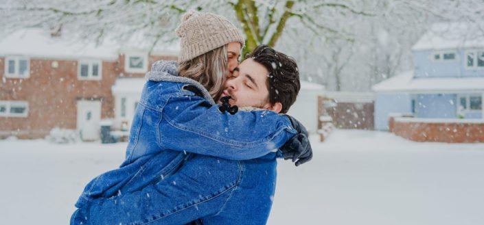 pareja siendo dulce el uno con el otro bajo una lluvia de nieve