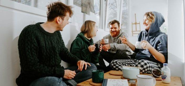 Grupo de amigos riendo y bebiendo juntos