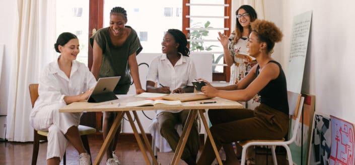 Grupo de mujeres discutiendo y mirando un portátil