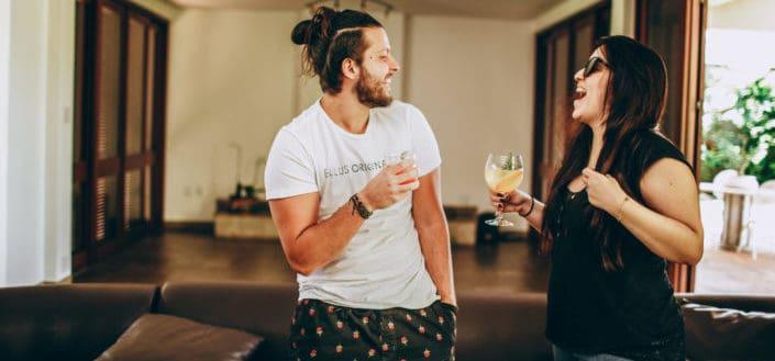 Pareja divirtiéndose mientras sostiene una bebida alcohólica