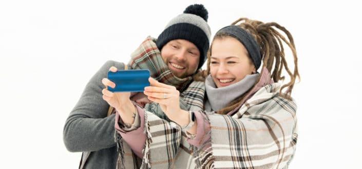 Pareja tomando un selfie mientras está cubierto con una manta