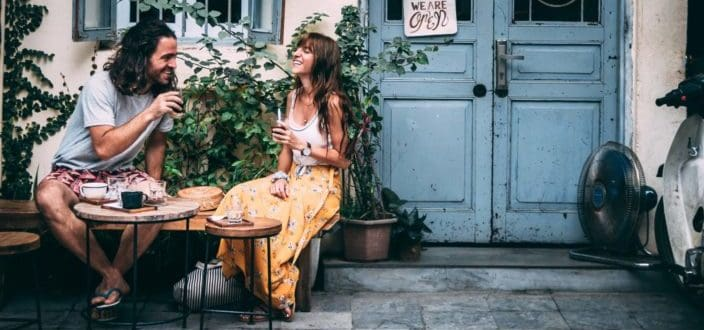 Pareja hipster tomando café fuera de una puerta azul