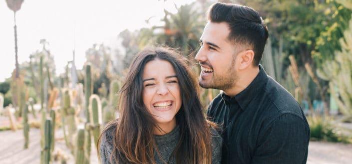 Pareja sonriendo mientras está de pie delante de cactus