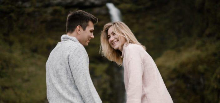 Pareja sonriendo el uno al otro frente a una cascada