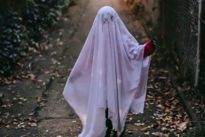 Chica con manta blanca como disfraz de Halloween